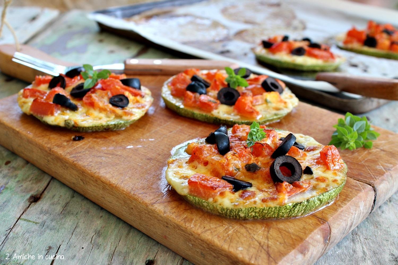 pizzette di zucchine tonde con pomodori a crudo , olive nere e basilico greco