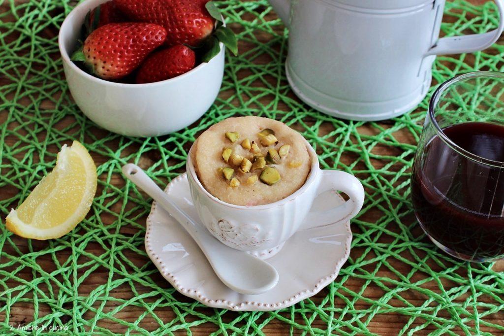 Mug cake al limone con fragole e pistacchi, ricetta per una colazione vegan e leggera.