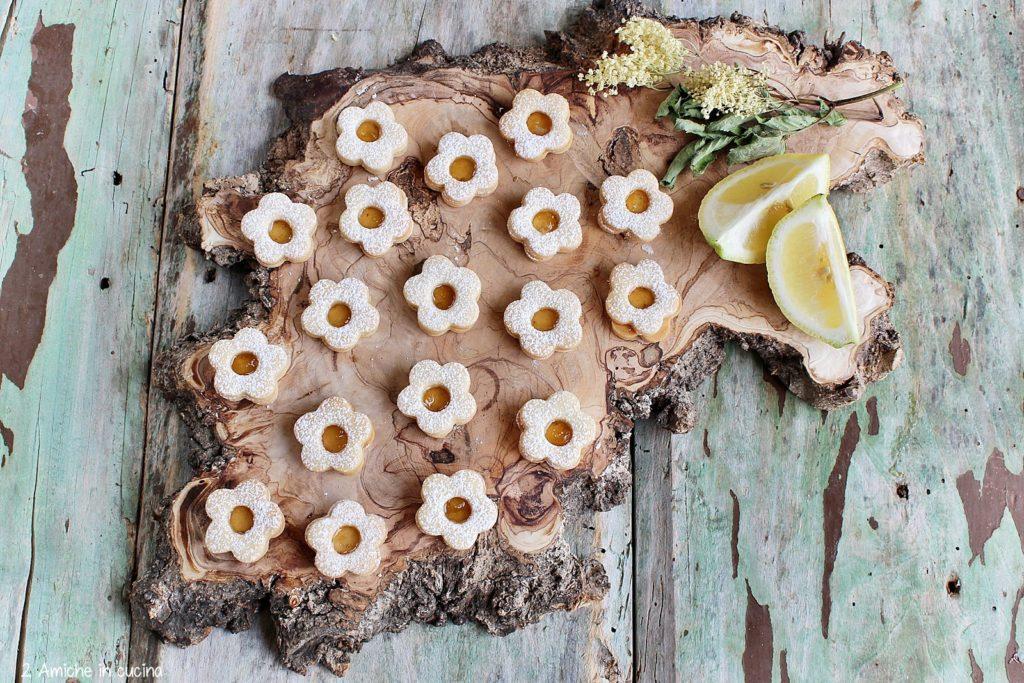 Fiorellini di frolla farciti con marmellata di limoni e fiori di sambuco.