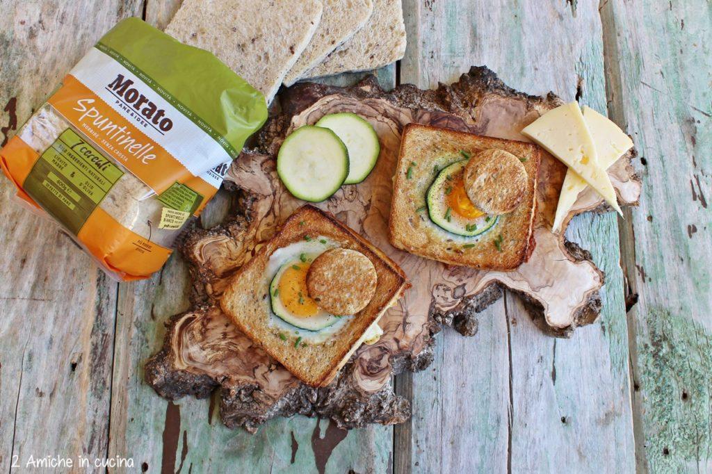 Uovo nel toast con pane ai cereali, zucchine, formaggio e cotto
