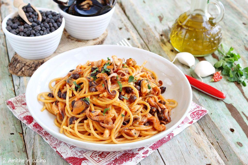 Piatto di spaghetti al pomodoro con pesce e legumi