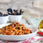 Piatto di spaghetti al pomodoro con polipetti, ceci e cozze