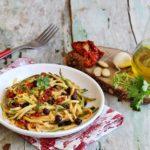 Piatto di spaghetti di zucchine conditi con pesto di pomodori secchi e ceci neri