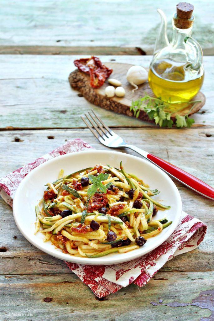 Piatto di spaghetti di zucchine, conditi con pesto di pomodori e mandorle