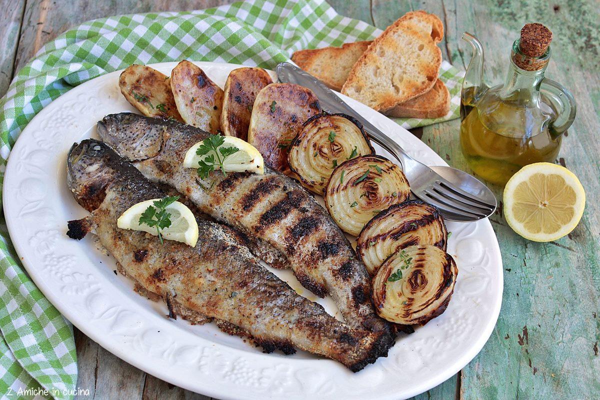 Trote cotte alla brace con contorno di patate e cipolle