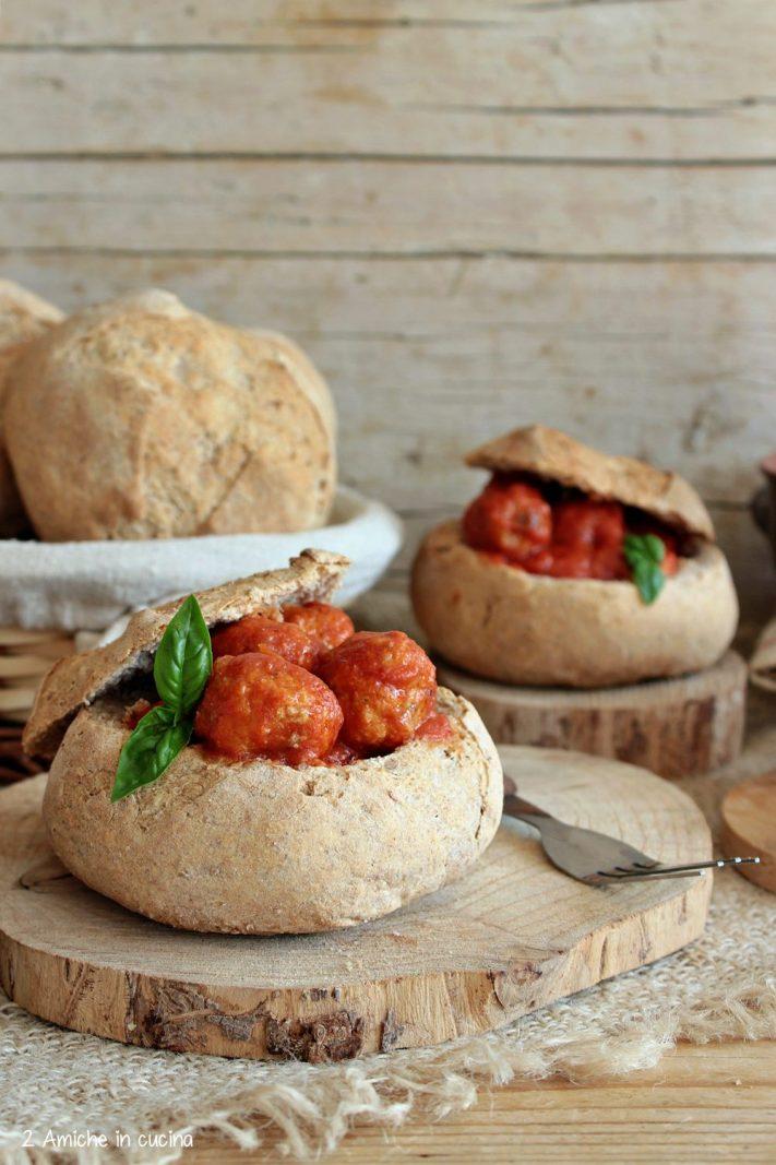Pagnottine di pan ner piena di polpette al sugo con uvetta e pinoli